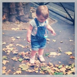 Little Miss Sunshine s'amuse avec les feuilles mortes sur le trottoir désert